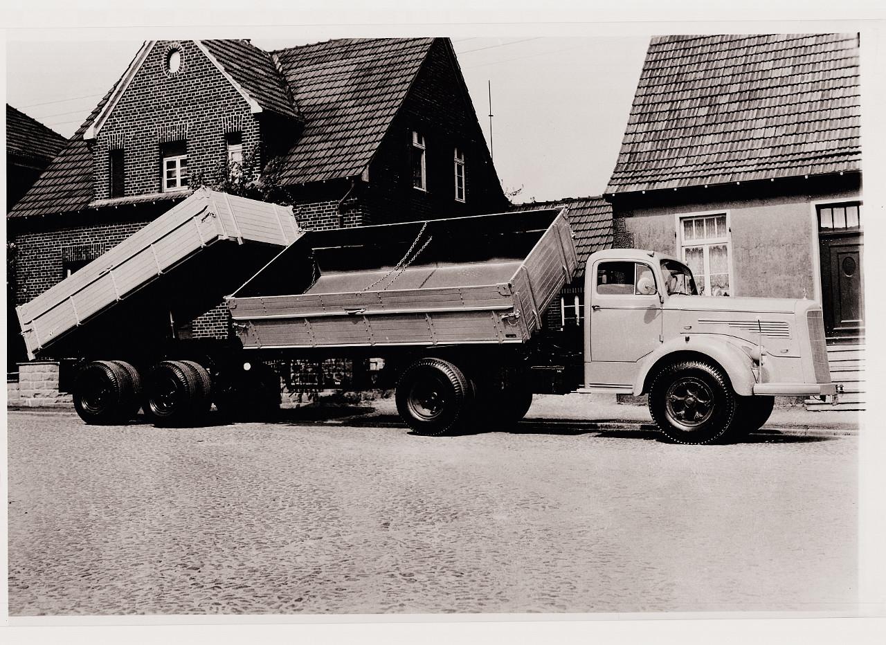 Oldalra billentő gépes kocsi, hátrabillentő tandemtengelyes pótkocsival, 1960-ból. Előnye, hogy lebillentéskor nem temeti be a saját kerekeit