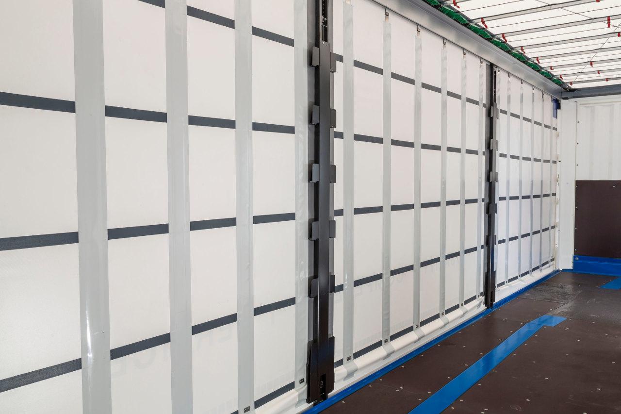 A Safe Curtain biztonsági függönyponyva előnye, hogy bedugható lécek helyett nagyon erős rugóacélból készült szalagokat építenek be a ponyva függőleges zsebeibe