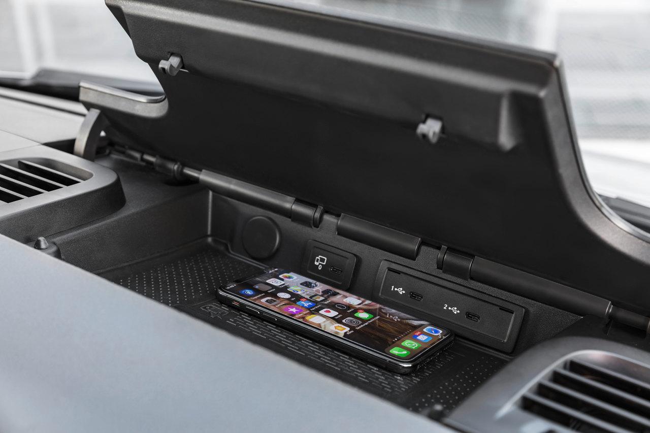 Vezeték nélküli töltő is rejlik a műszerfal felső tárolójában. Előrelátó megoldás, hogy az USB-csatlakozók már mind C típusúak, bár ma még többnyire A-C kábelt mellékelnek az eszközök mellé. Természetesen igény szerint 12 voltos csatlakozó, illetve 230 voltos konnektor is elérhető