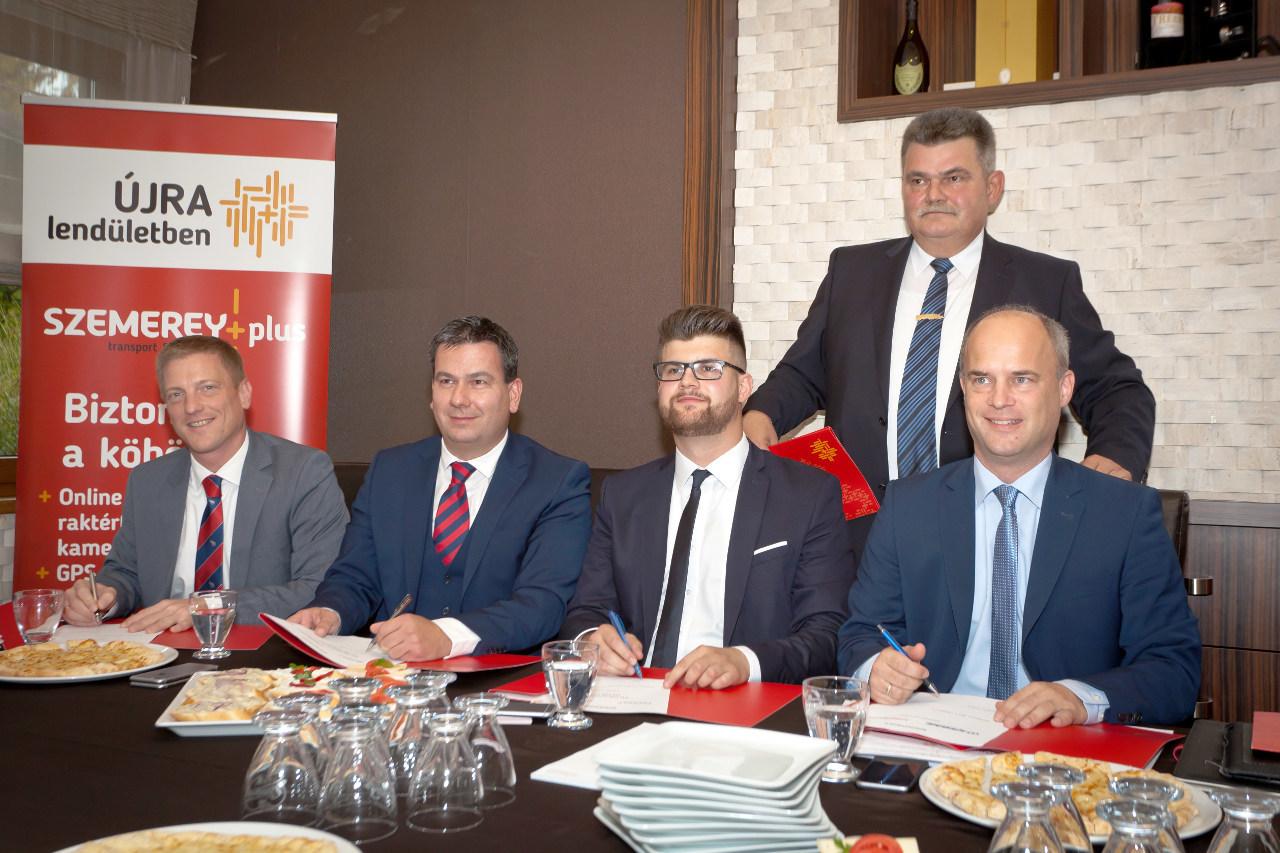 A beszerzési szerződés aláírói balról jobbra: Kolnhofer Bálint, a Schmitz Cargobull Magyarország Kft. ügyvezető igazgatója, Pais József, a Pappas Auto Magyarország Kft. ügyvezető igazgatója, Szemerey Péter, a Szemerey   Plus Zrt. vezérigazgatója és Somlai Roland, a Krone Trailer SE Kft. értékesítési vezetője. A háttérben: Szemerey Lóránd